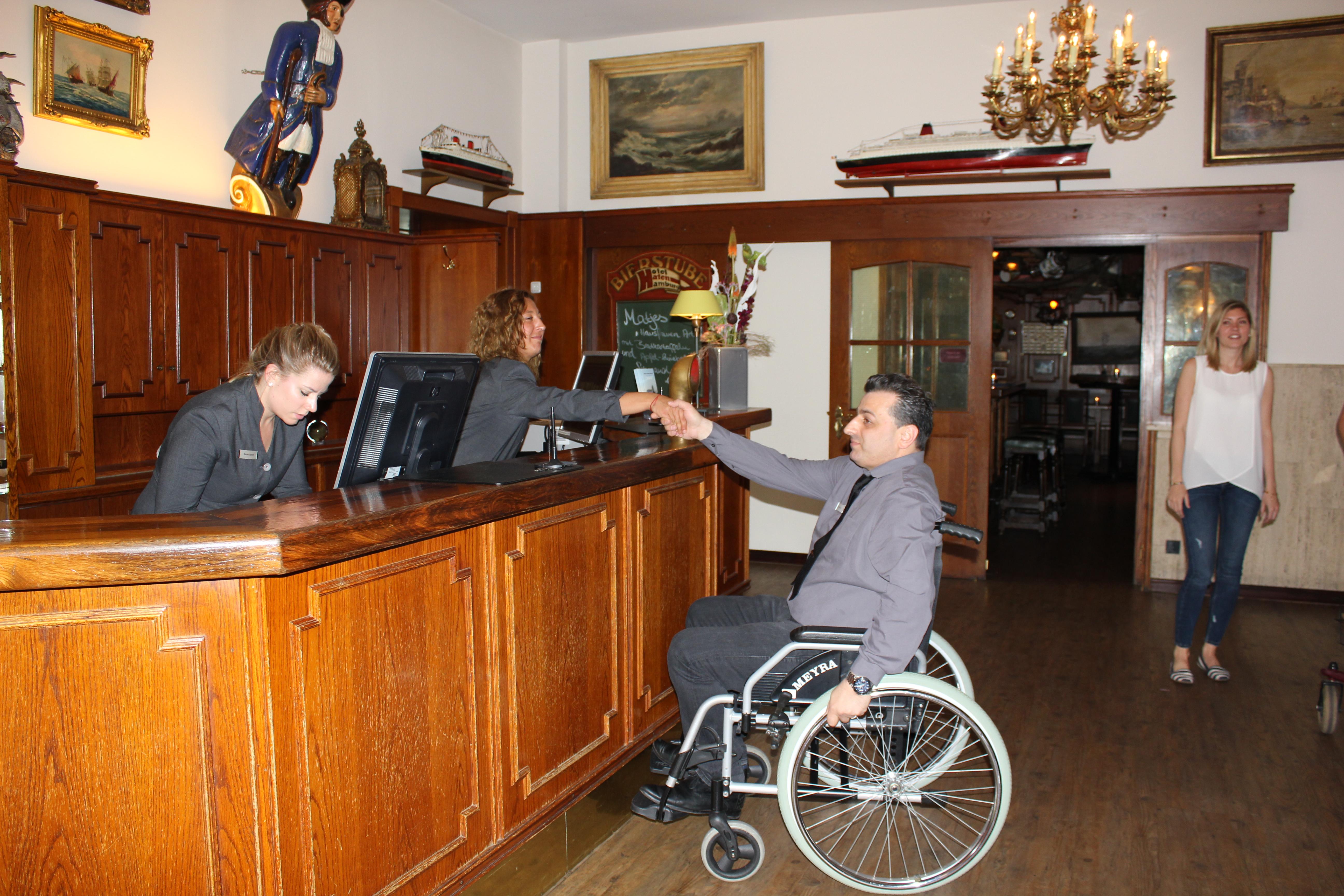 Mann im Rollstuhl an der Rezeption