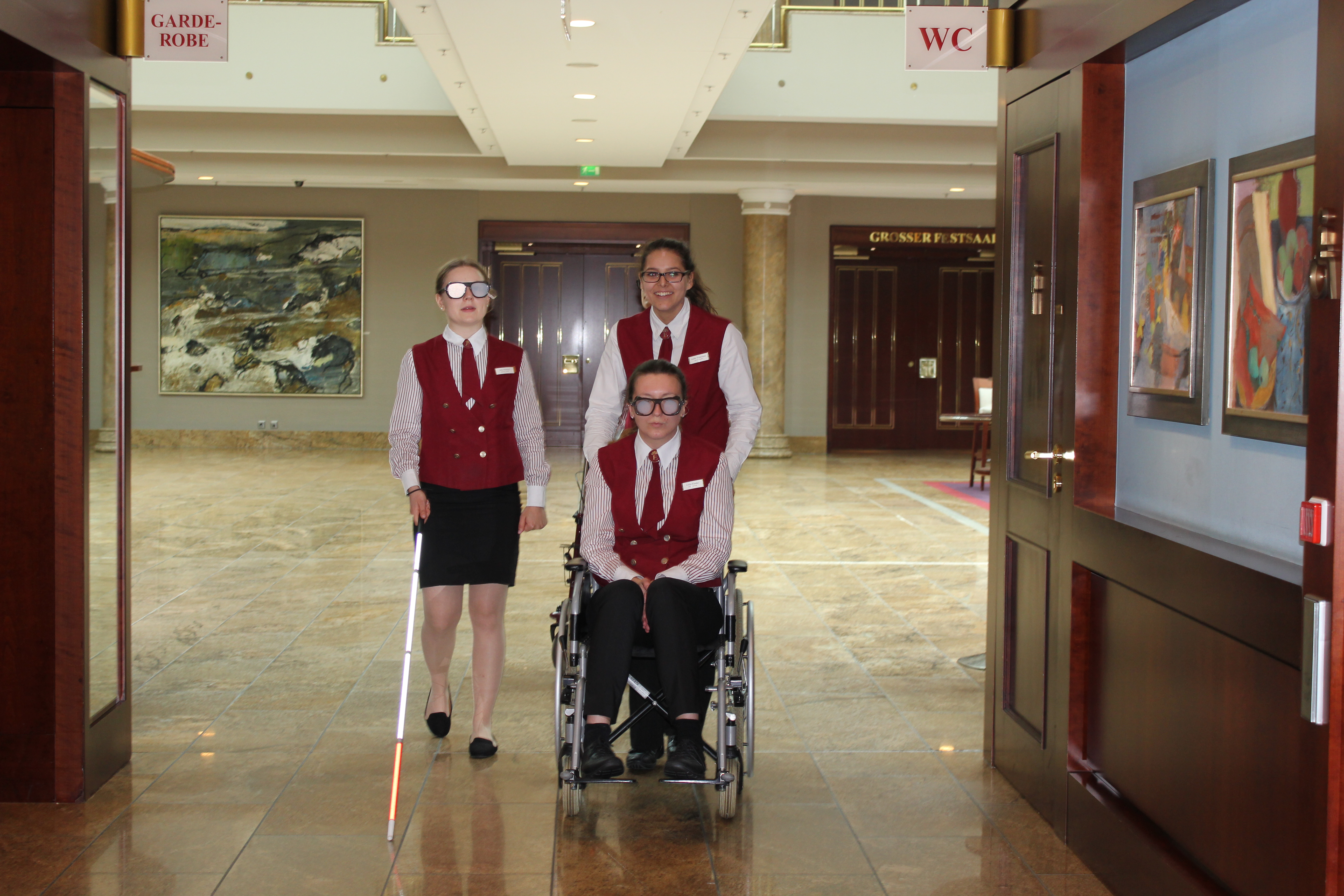 Drei Frauen, eine wird im Rollstuhl geschoben
