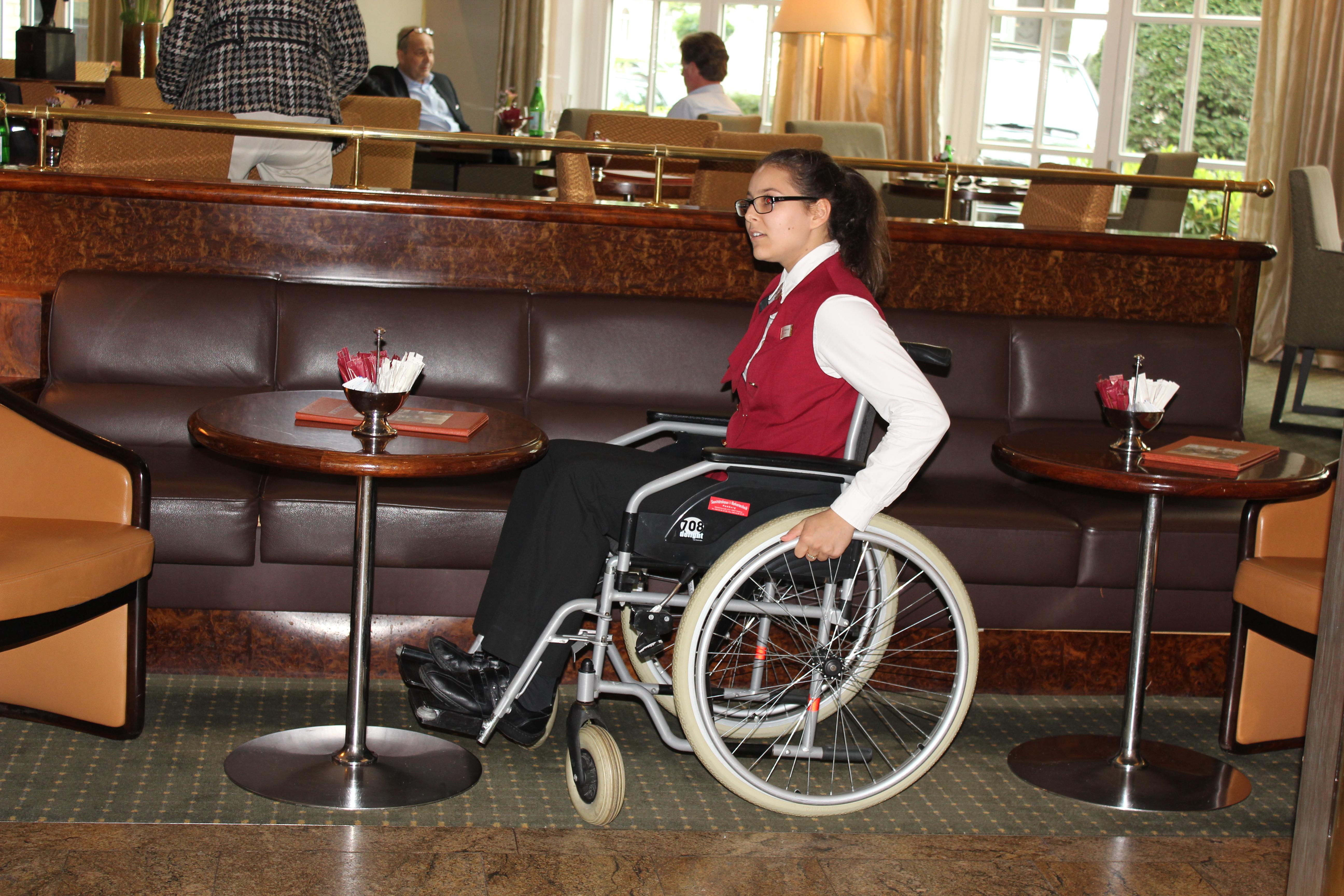 Frau im Rollstuhl im Restaurant eines Hotels