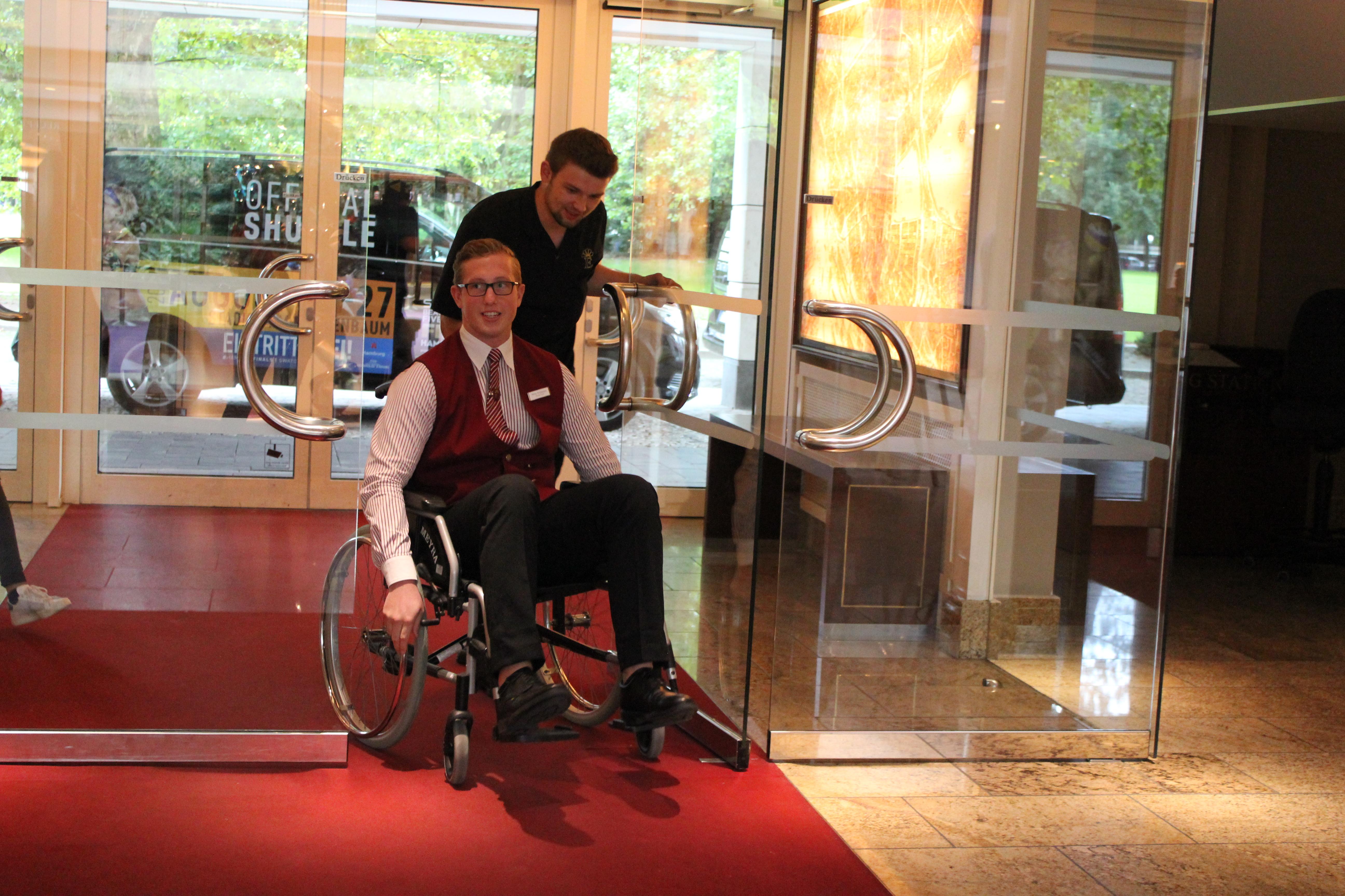 Rollstuhlfahrer und Begleitung betreten das Hotel