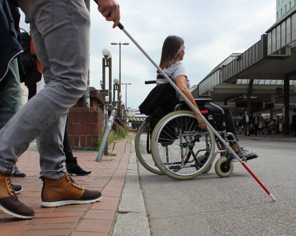 Frau mit Rollstuhl und Person mit Taststock überqueren Strasse
